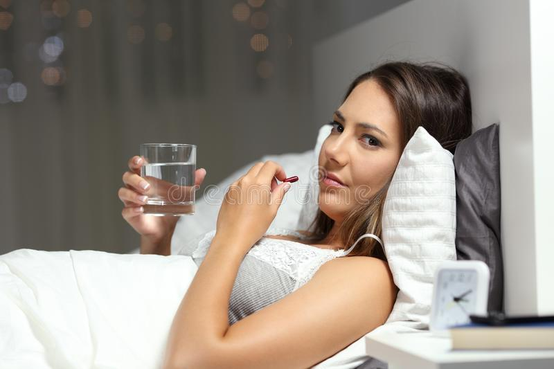 Ill woman looks at you taking pill in the night on the bed royalty free stock photography