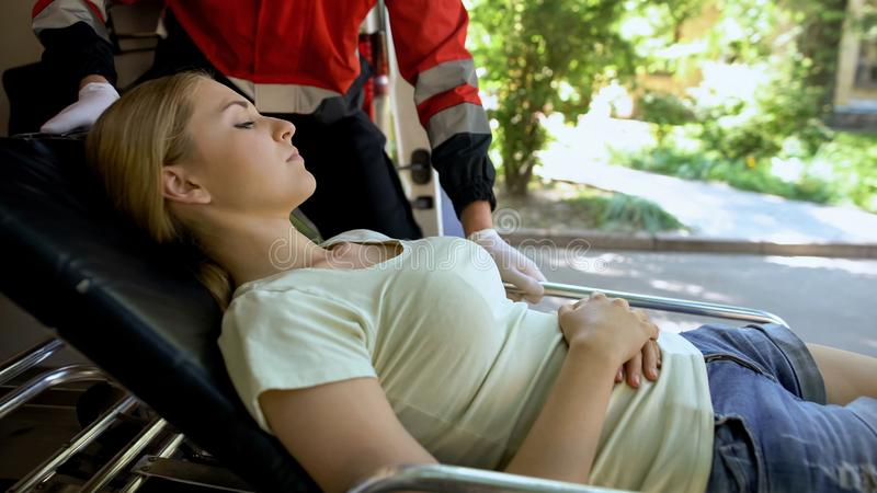 Ill woman lying on stretcher, ambulance crew transporting patient to clinic. Ill women lying on stretcher, ambulance crew transporting patient to clinic, stock royalty free stock photography
