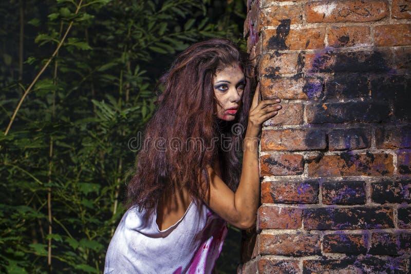 Illavarslande sexig kvinna i en blodig skjorta på den mörka tegelstenväggen arkivbilder