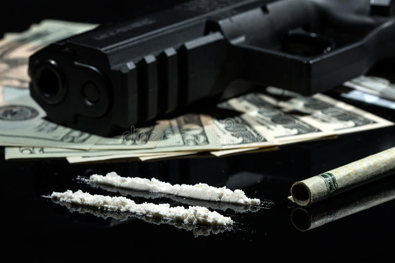 Illegal drugs , money and guns. Close up shot of cocaine, US dollars an a gun, on black background royalty free stock images