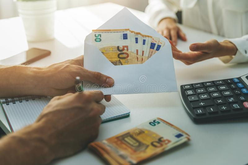 Illegal employment tax evasion concept - hand giving envelope with cash money. In office royalty free stock image