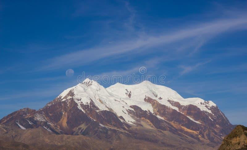Illimani berg och fullmåne royaltyfria foton