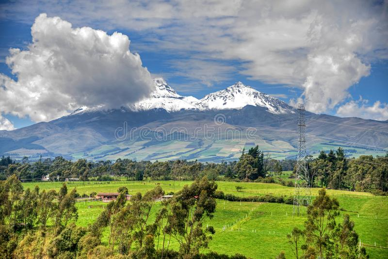 The Illinizas volcano. Beautiful view of the snow caped Illinizas volcano, in the Ecuadorian Andes, on a sunny and overcast morning royalty free stock photo