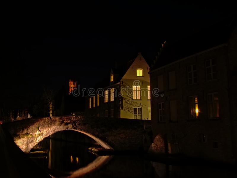 Old bridge and houses in Bruges at night. Illluminated old stone bridge over a canal with houses on the side in the medieval city of Bruges, Flanders, Belgium stock image