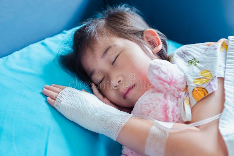 Illness asian child admitted in hospital with saline intravenous on hand stock photography