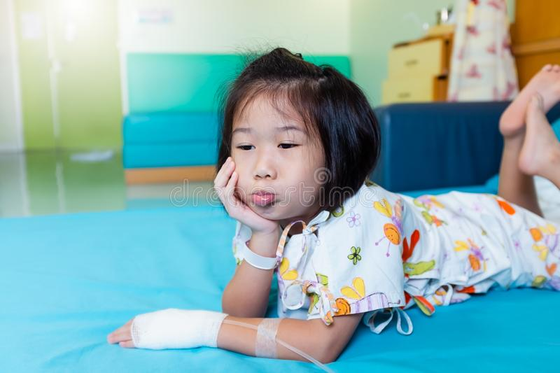 Illness asian child admitted in hospital with saline intravenous on hand royalty free stock photos