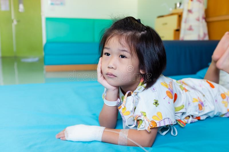 Illness asian child admitted in hospital with saline intravenous on hand royalty free stock photography