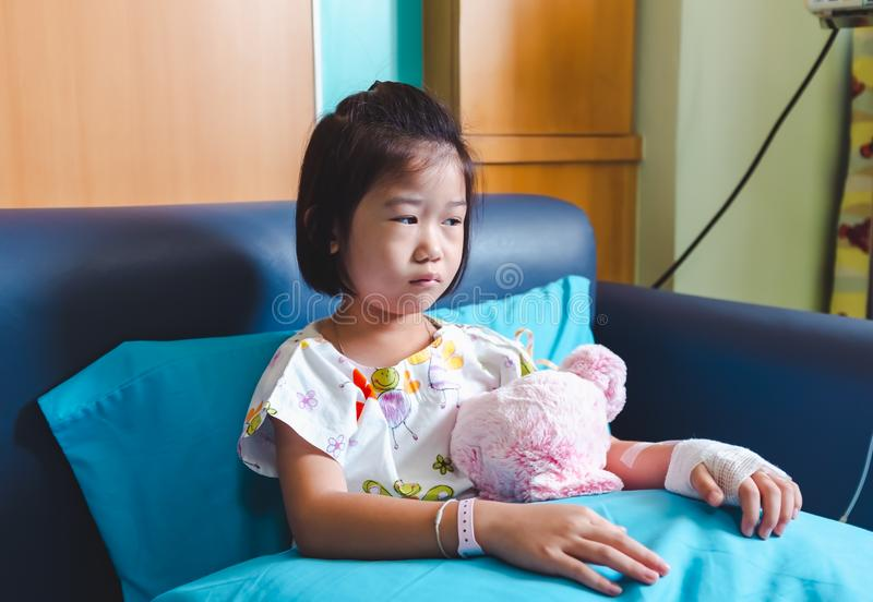Illness asian child admitted in hospital while saline intravenous IV on hand . stock photos
