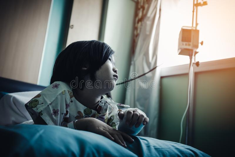 Illness asian child admitted in hospital with saline iv drip on hand.  Health care stories royalty free stock photos