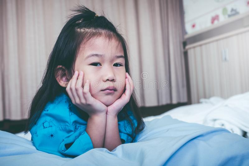 Unhappy illness asian child admitted in hospital. Vintage tone. stock photos