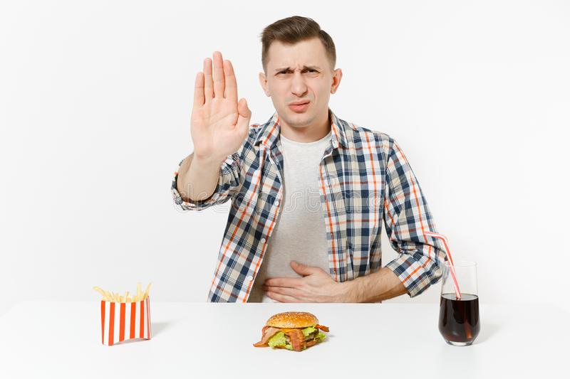Illness man put hands on pain abdomen, stomach-ache at table with burger, french fries, cola in glass isolated on white. Background. Proper nutrition or royalty free stock image