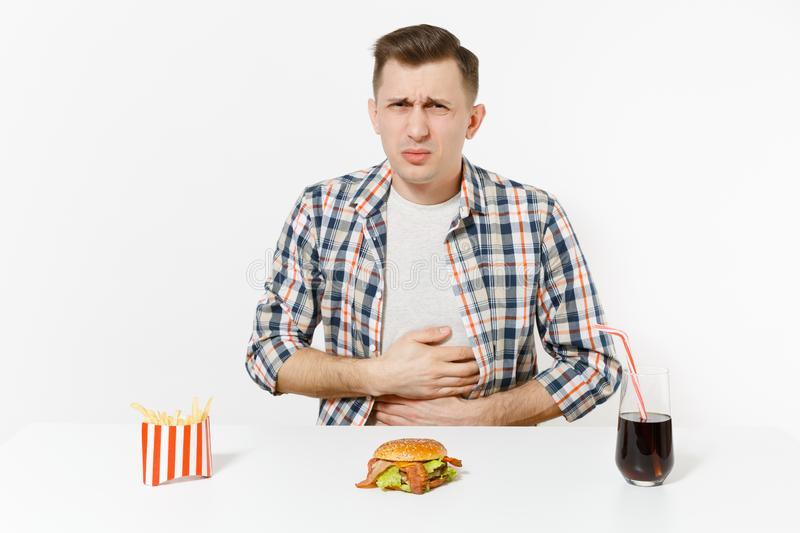 Illness man put hands on pain abdomen, stomach-ache at table with burger, french fries, cola in glass isolated on white. Background. Proper nutrition or royalty free stock photos