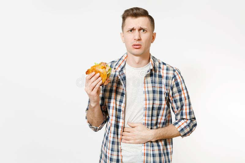 Illness sad young man in shirt put hand on pain abdomen, stomach-ache, standing and holding burger isolated on white. Background. Proper nutrition or American royalty free stock image