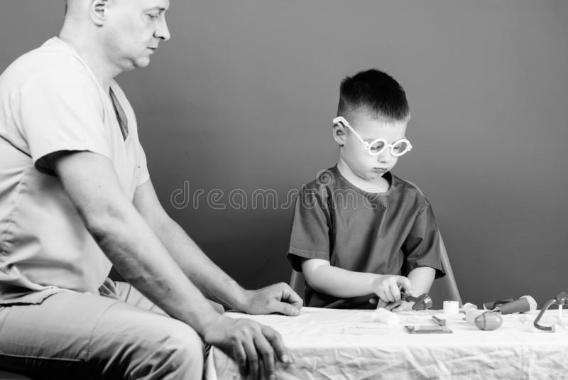 Illness treatment. Dad and son medical dynasty. Medical examination. Boy cute child and his father doctor. Hospital. Worker. Health care. Medicine concept. Kid royalty free stock photo