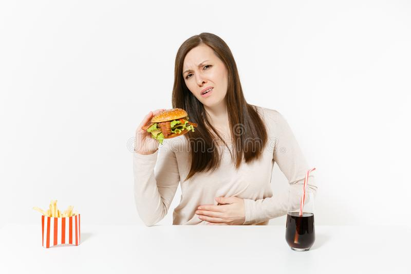 Illness woman put hand on pain abdomen, stomach-ache at table with burger, french fries, cola in glass bottle isolated. On white background. Proper nutrition or royalty free stock photography