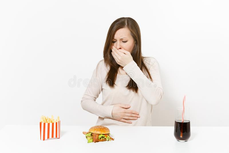 Illness woman put hand on pain abdomen, stomach-ache at table with burger, french fries, cola in glass bottle isolated. On white background. Proper nutrition or stock photo