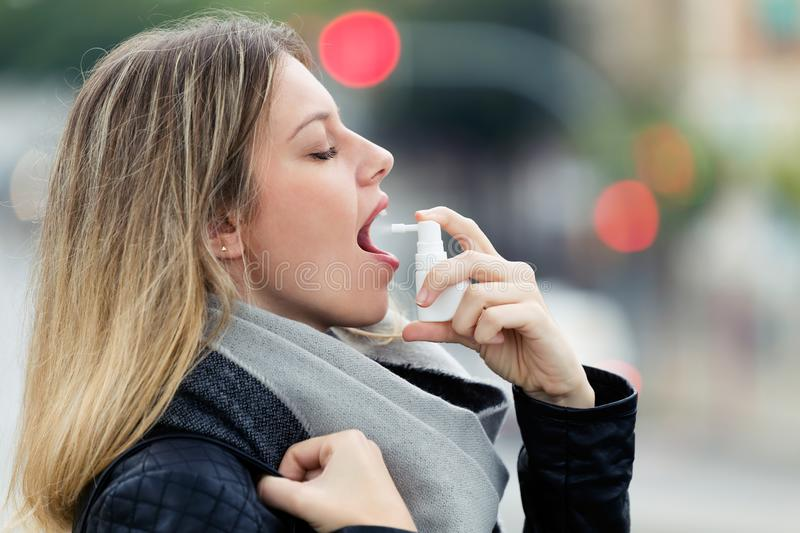 Illness young woman applying a analgesic spray to soften the throat in the street. stock images