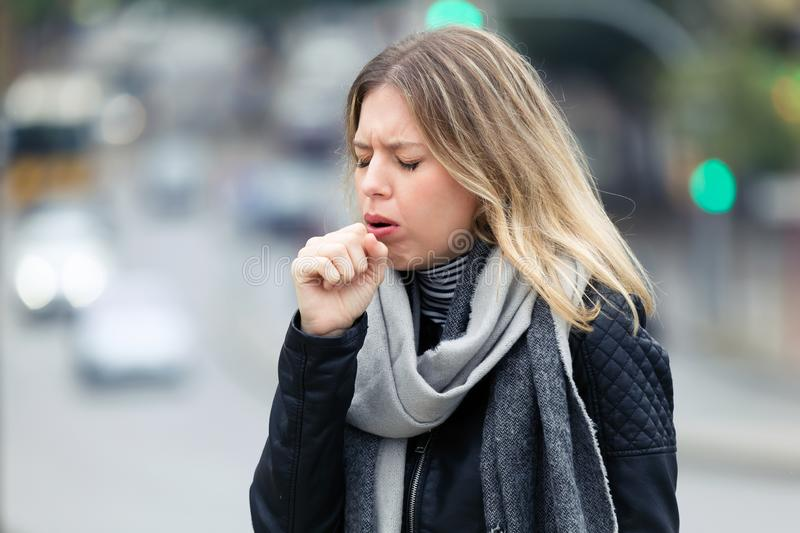 Illness young woman coughing in the street. Shot of illness young woman coughing while walking in the street stock images