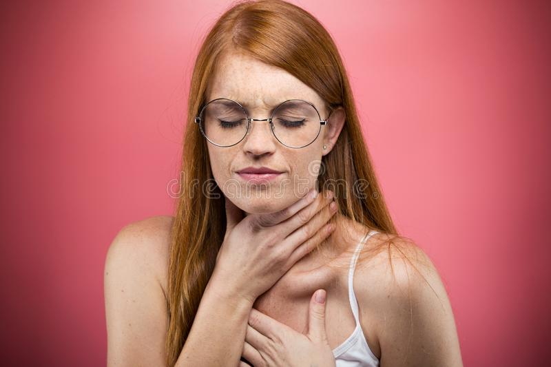Illness young woman with terrible throat pain over pink background stock photos