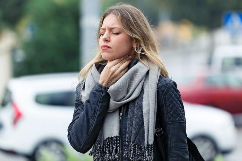 Illness young woman with terrible throat pain walking to the street. royalty free stock images