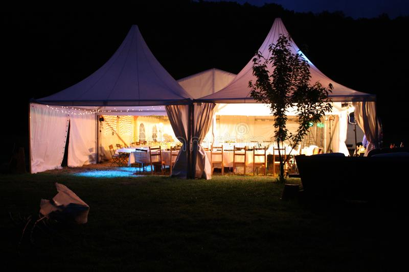 Illuminated afternoon dinnerparty tent stock images