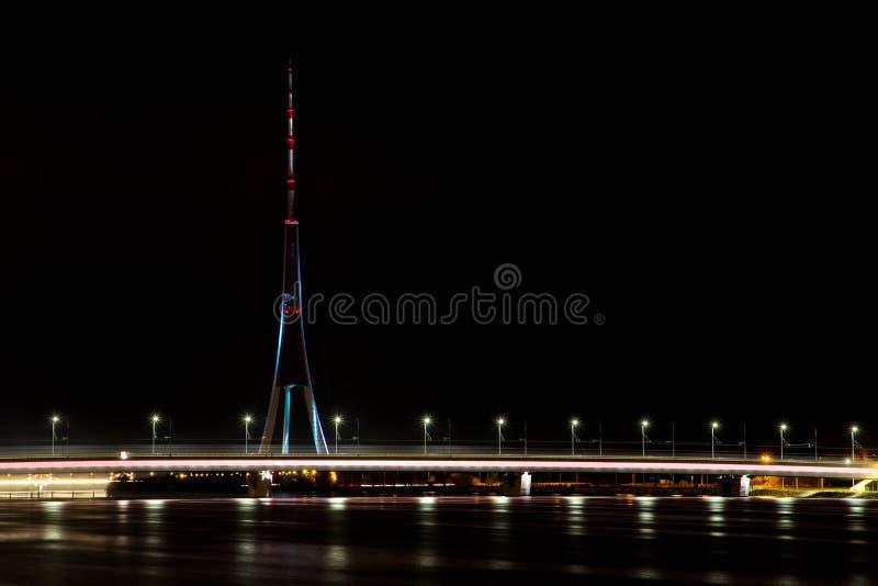Illuminated Akmens Bridge crossing Daugava river and Riga Radio and TV Tower royalty free stock photos