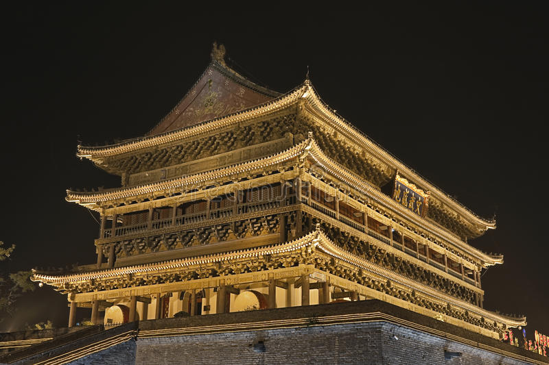 Illuminated ancient Drum Tower at the ancient city wall by night time, Xian, Shanxi Province, China. The illuminated ancient Drum Tower located at the ancient stock image