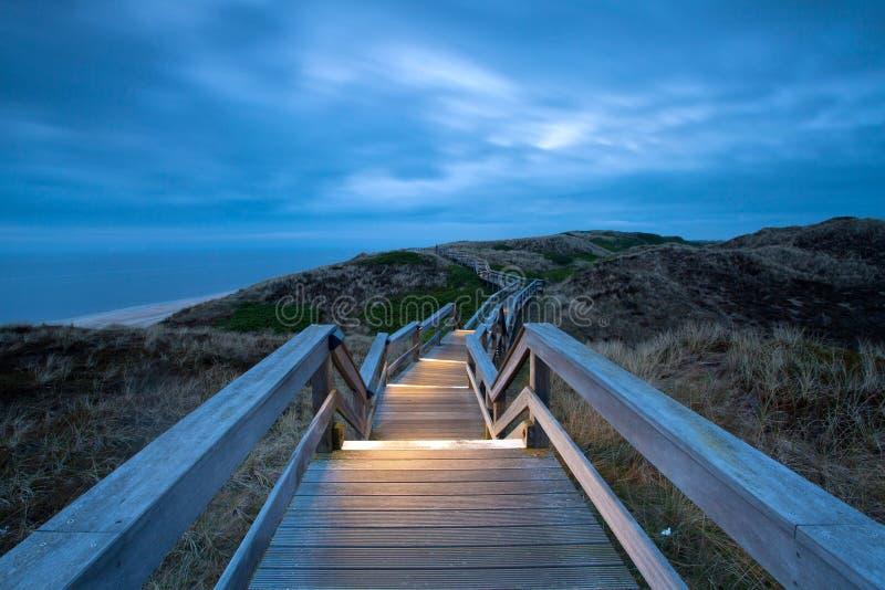 Illuminated boardwalk. Illuminated Wooden boardwalk through dunes at the North sea beach in Germany royalty free stock photography