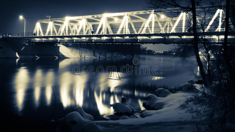 Illuminated bridge at night in winter royalty free stock photography