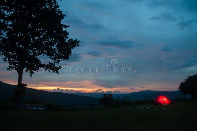 Illuminated camping tent at twilight under sunset sky on the mountain peak. Thai-Laos border. Phu Suan Sai National Park, Na Haeo. Loei, Thailand. Winter stock image