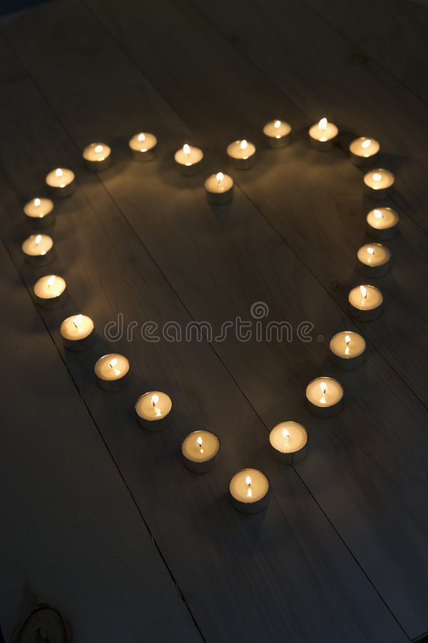 Illuminated Candles Placed In A Heart Shape stock images