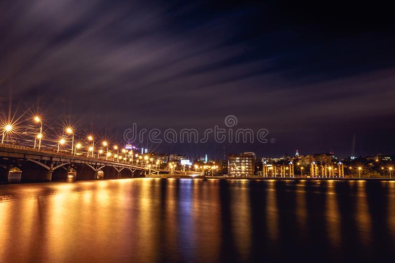 Illuminated Chernavsky bridge at night, view to right bank or downtown of Voronezh city, dramatic cityscape with reflection. In water stock images