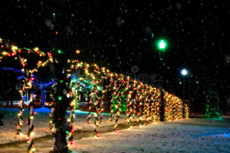 Illuminated Christmas arched tunnel walk. A lighted tunnel of brightly lit arches forms the centpiece of a village outdoor Christmas display royalty free stock photography