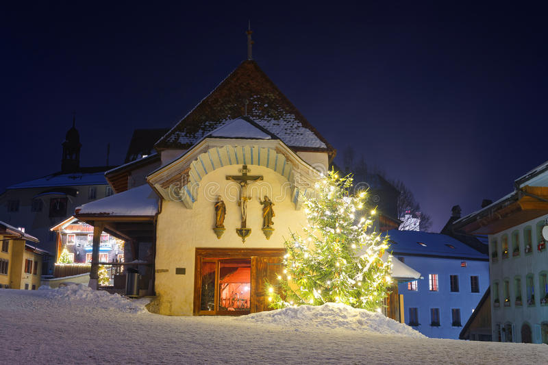 Illuminated Christmas fir tree in front of the church in Gruyere. Beautifully decorated and illuminated Christmas fir tree in front of the church in Gruyere stock images