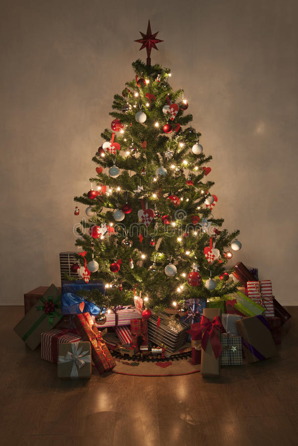 Illuminated christmas tree with presents. Beautiful christmas tree with lights and presents royalty free stock image