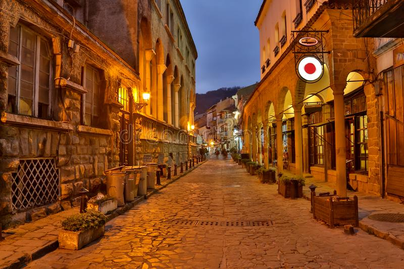 Illuminated cobbled street with light reflections on cobblestones in old historical city by night. Dark blurred royalty free stock photos