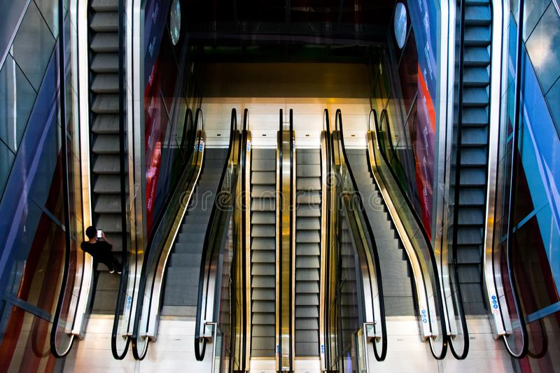 Illuminated and colored escalators in a mall royalty free stock images