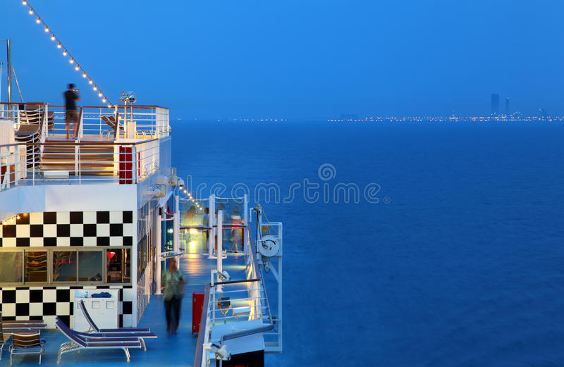 Illuminated cruise ship with people on deck