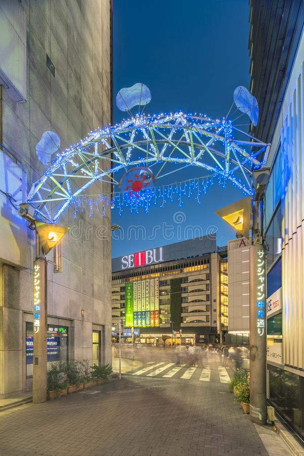 Illuminated entrance gate with security camera operating at the Sunshine Central Street connecting the east exit of Ikebukuro. Station lines with yakitori and royalty free stock photo