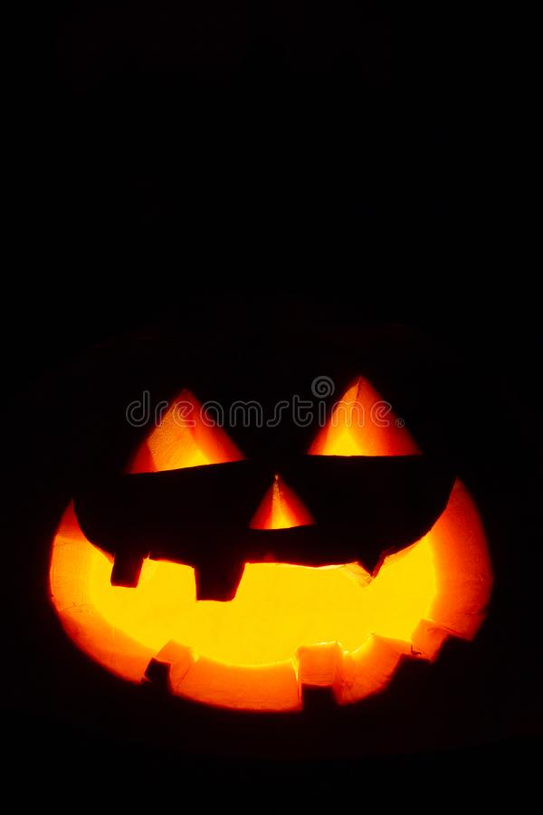 Illuminated eyes and mouth of jack-o`-lantern Halloween pumpkin on dark background stock image