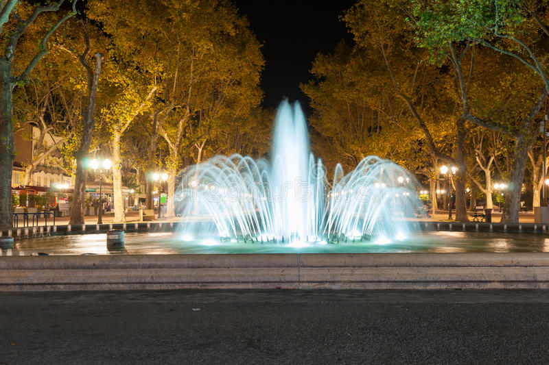 Illuminated fountain and tree lined promenade long exposure nigh. T scene at end of Place de le Comedie Montpellier France urban & architectural royalty free stock photography