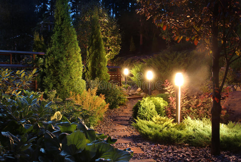 Illuminated garden path patio. Illuminated home garden path patio lights and plants in evening dusk royalty free stock images