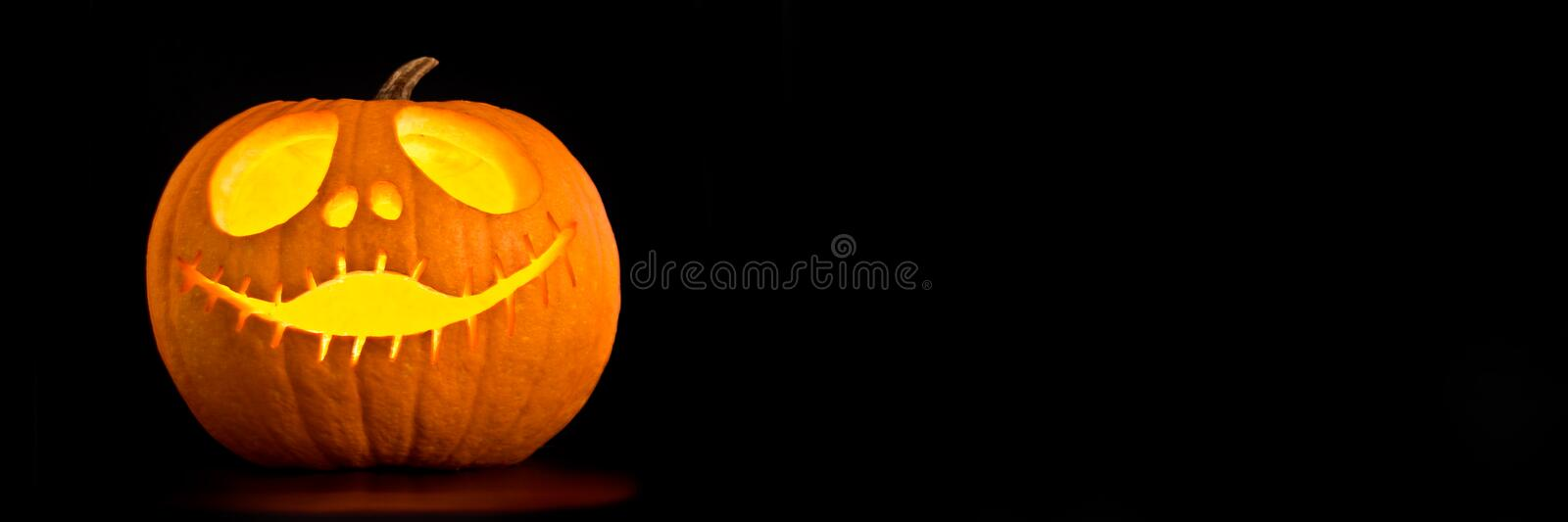 Illuminated Halloween Jack-o-lantern pumpkin black panoramic background with copy space. Illuminated Halloween Jack-o-lantern pumpkin, black panoramic background stock images