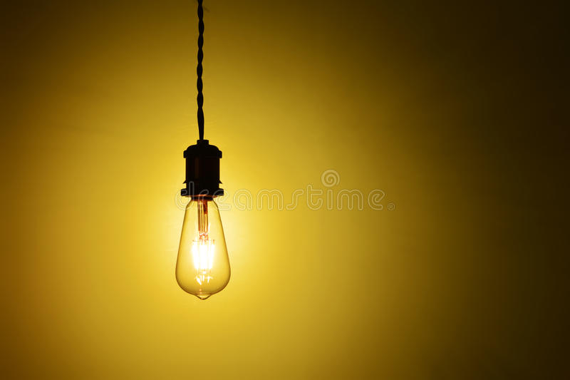 Illuminated hanging led lamp bulb. New type hanging led lamp bulb over orange background.three generations of light bulb such as regular incandescent lamp bulb royalty free stock image