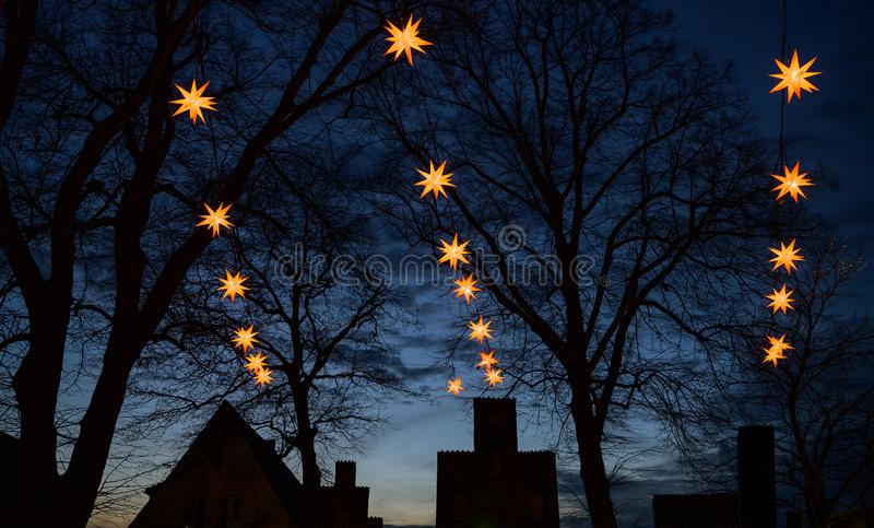 Illuminated Herrnhuter Moravian Christmas stars hanging above the dark silhouettes of old house gables and big trees against a stock photography