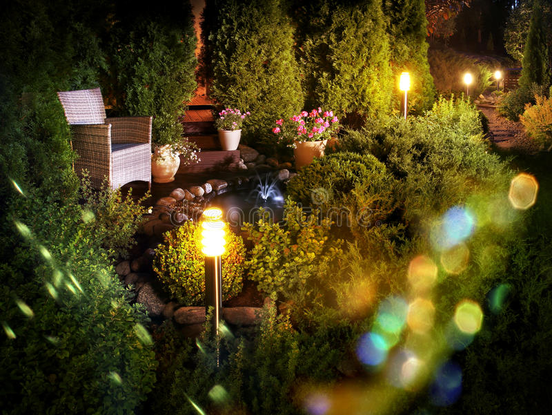 Illuminated home garden fountain patio. Illuminated home garden patio plants and evening party lights near small fountain royalty free stock photography
