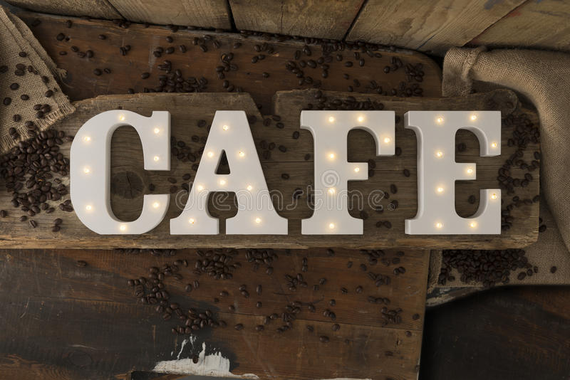 Illuminated Letters Spelling CAFE with Coffee Beans on Wooden Surface stock images