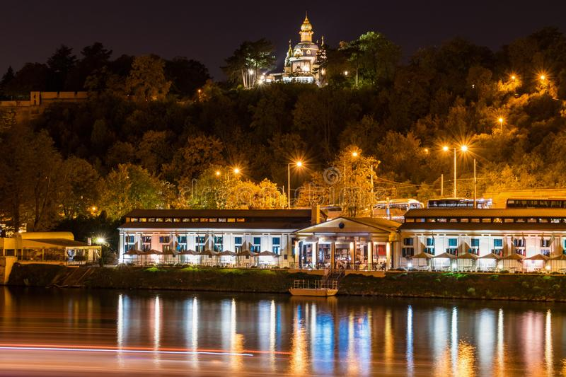 Illuminated marina building with colored reflections in water at night in Prague royalty free stock image