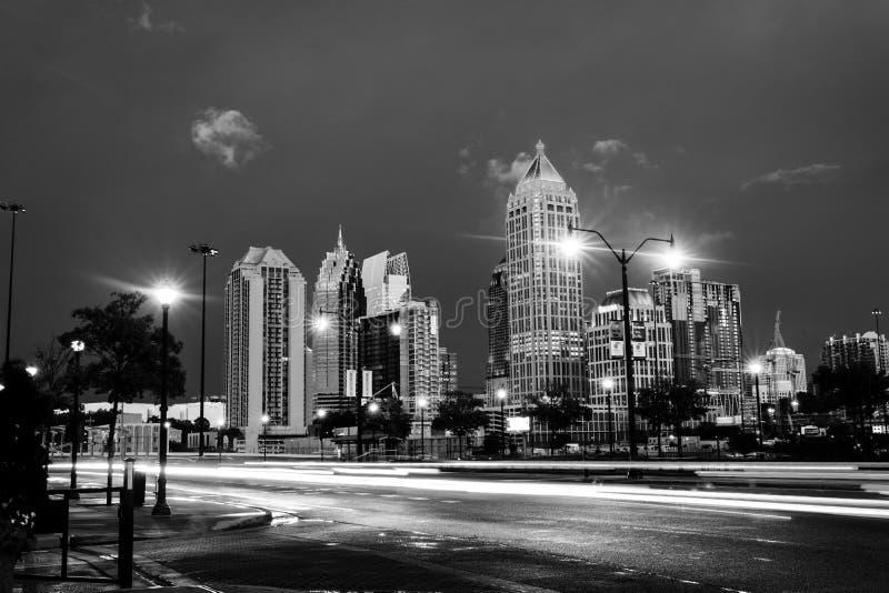 Illuminated Midtown in Atlanta, USA at night. Car traffic, illuminated buildings and dark sky. Black and white royalty free stock image