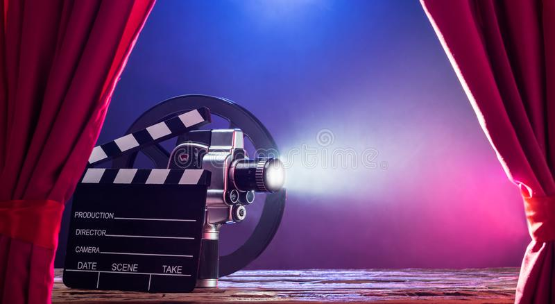 Movie Camera With Clapperboard And Film Reel On Stage royalty free stock photos
